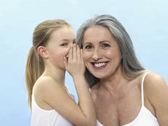 Stock Photo of granddaughter wispering in grandmothers ear, portrait