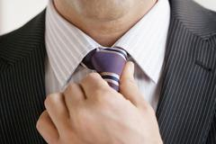 Stock Photo of business man adjusting tie, close up
