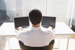 Business man using two laptops, back view Stock Photos