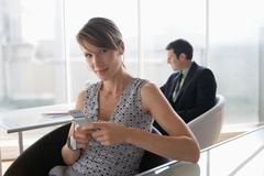 Business woman using mobile phone, male colleague in background Stock Photos