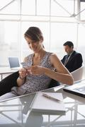 Business woman using a mobile phone, male colleague in background Stock Photos