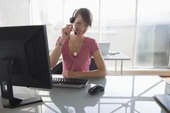 woman working on computer, wearing headset - stock photo
