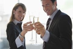 business woman and business man toasting with sparkling wine - stock photo