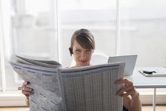 Woman reading financial newspaper Stock Photos