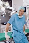 surgeon sitting on operating table - stock photo