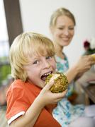 boy holding bread roll,mother in background - stock photo