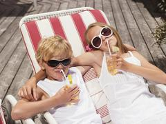 brother and sister lying in deck chairs, drinking juice - stock photo