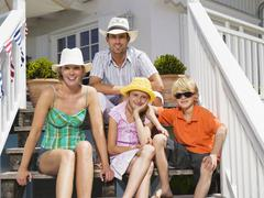 Family sitting in front of house Stock Photos