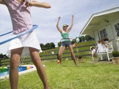 family in garden, playing with hula-hoops - stock photo