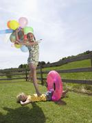 girl, holding balloons, jumping over boy - stock photo