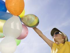 Stock Photo of boy holding balloons, portrait