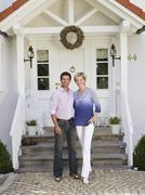 Couple standing in front of house Stock Photos