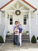 Stock Photo of family with baby standing in front of house