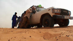 A UN type jeep gets stuck in the sand on a road in rural Mali. Stock Footage