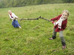 germany, two girls (6-7), (8-9) playing tug of war - stock photo