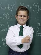 Boy (10-11) leaning against blackboard, smiling, portrait, close-up Stock Photos