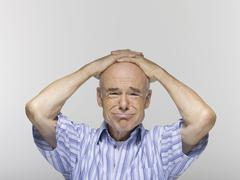Senior man, hands clasped on head, portrait, close-up - stock photo