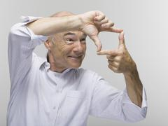 Portrait of a senior man, gesturing with one hand above the other Stock Photos