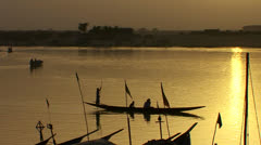 Boats are rowed on the Niger River in beautiful golden light in Mali, Africa. Stock Footage