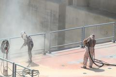 Sandblasting of metal structures at construction site Stock Photos