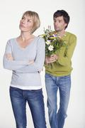 Stock Photo of Young couple, man with flowers, portrait