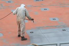 worker painting ship hull using airbrush gray paint - stock photo