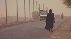 A Touareg person walks down a road through the Sahara desert in Mali during a Stock Footage