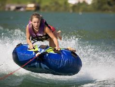 Stock Photo of Austria, Moon Lake, Girl (16-17)  riding water sled
