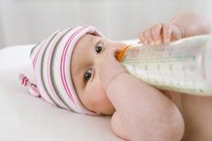 Baby boy  (6-9 months) drinking milk from bottle, portrait Stock Photos