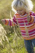 Little girl (2-3) playing in meadow, close-up - stock photo