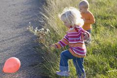 Stock Photo of Boy (1-2) and girl (2-3) playing with balloons