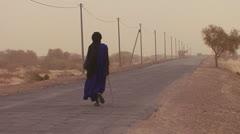 A Touareg person walks down a road through the Sahara desert in Mali. Stock Footage