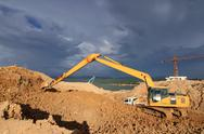 Stock Photo of excavator loader machine during earthmoving works outdoors at construction si