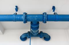 blue pipe line with blue valve on  wall - stock photo