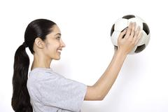 Female soccer fan holding soccer ball,  portrait - stock photo