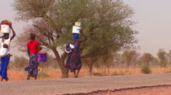 Women walk carrying goods on their heads through the Sahara desert in mali. Stock Footage