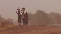 Women walk carrying goods on their heads through the Sahara desert in mali. Stock Footage