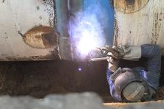 male welder worker wearing protective clothing fixing welding   and sewerage  - stock photo