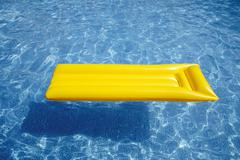 Yellow airbed floating in pool, elevated view - stock photo