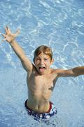 Boy (10-11) fooling about in swimming pool Stock Photos