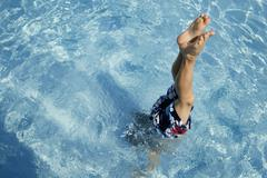Boy (10-11) performing hand stand in pool - stock photo