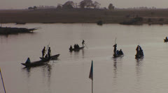 Boats are rowed in silhouette on the Niger River in mali, Africa. Stock Footage