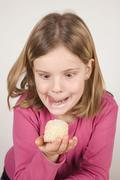 Girl (6-7) looking at chocolate marshmallows, fooling about Stock Photos