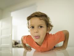 Portrait of young boy (4-5), sticking out tongue Stock Photos