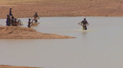 Children use conical nets to catch fish in a pool along a river in mali, Africa. Stock Footage