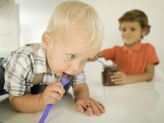 Stock Photo of Two boys (4-5), (12-24 months), boy licking chocolate from spoon, portrait