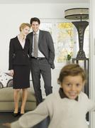 Family standing in livingroom, portrait Stock Photos