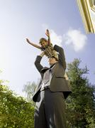 Father holding son (4-5) up on air Stock Photos