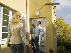 Father at door holding boy (3-4), mother coming home Stock Photos
