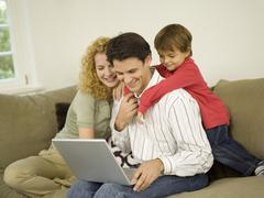 Young family in living room, father using laptop - stock photo